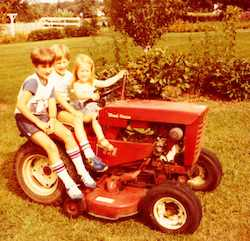 kids on a riding lawn mower