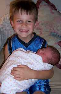 swaddled infant with brother
